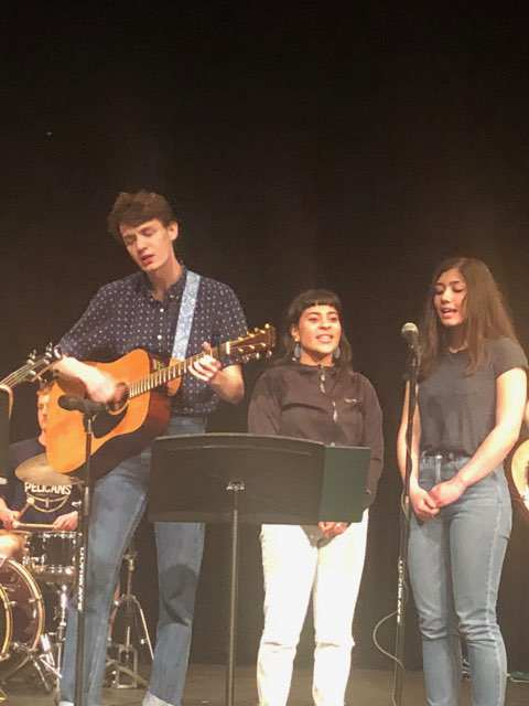 Grant plays guitar while singing with, Naomi and Anevay. Trey on drums.